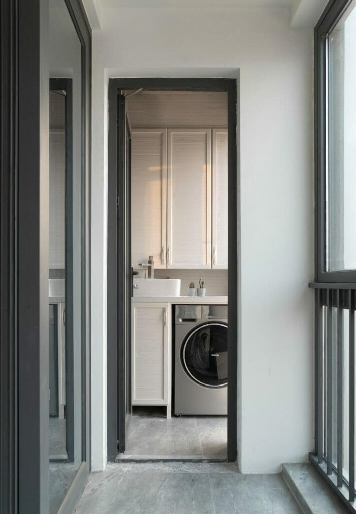The balcony has a washing machine and a cupboard to let clothes dry