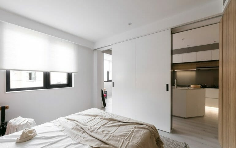 bedroom with sliding doors made of industrial wood - small studio apartment