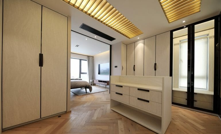 Dressing room with many industrial wooden cabinets with skylights, glass doors and wooden cabinets
