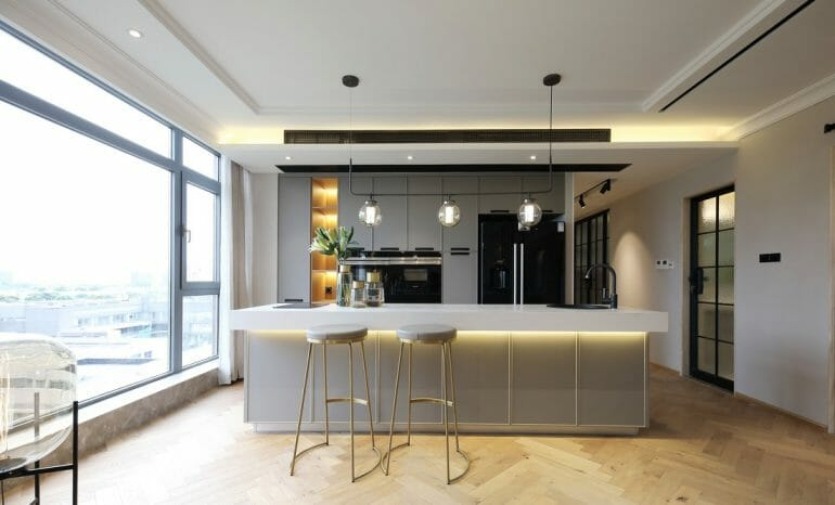 Kitchen bar made of artificial stone, high waiting chairs and cozy yellow led lighting - interior of nordic