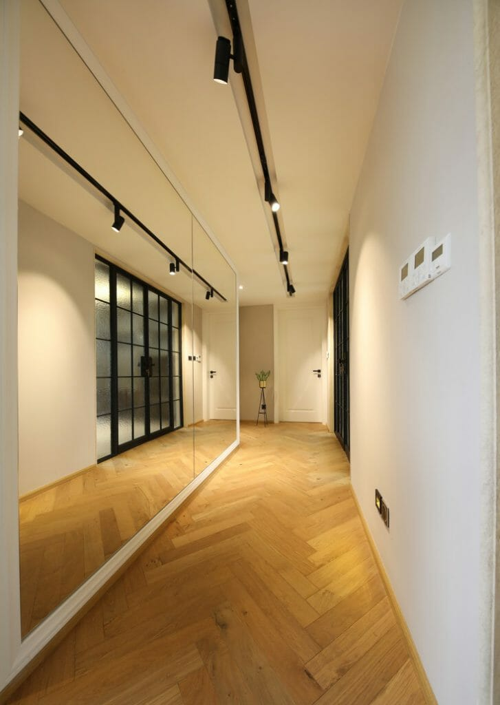 The hallway is designed with a mirror wall, artistic ceiling lights, fish-bone-shaped wooden floors - Nordic interior.