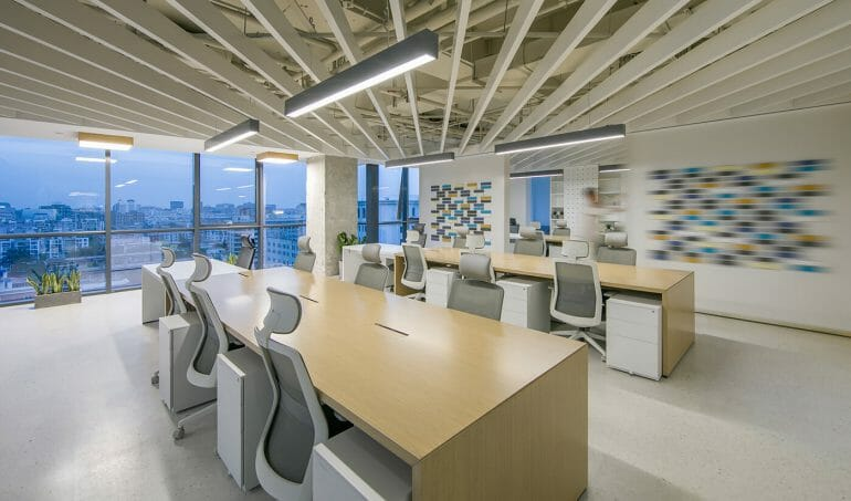 The working area is spacious, with modern office chairs and tables with headrests, above are led lights